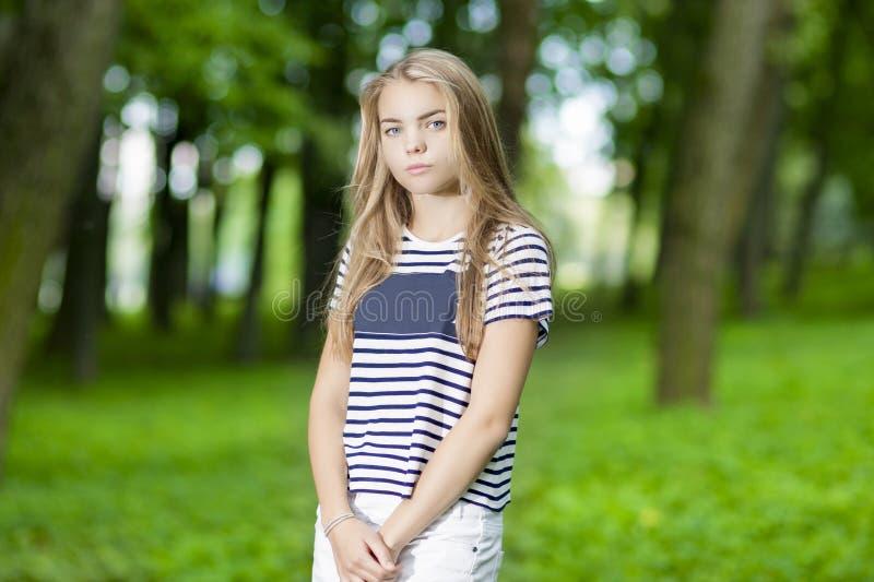 Adolescent caucasien blond posant dans la forêt verte photographie stock