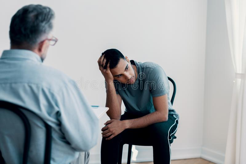 Adolescent déprimé semblant parti tout en parlant à son thérapeute photo libre de droits