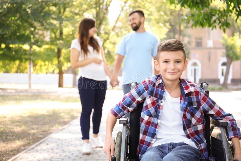 Adolescent dans le fauteuil roulant avec sa famille marchant dehors photographie stock libre de droits