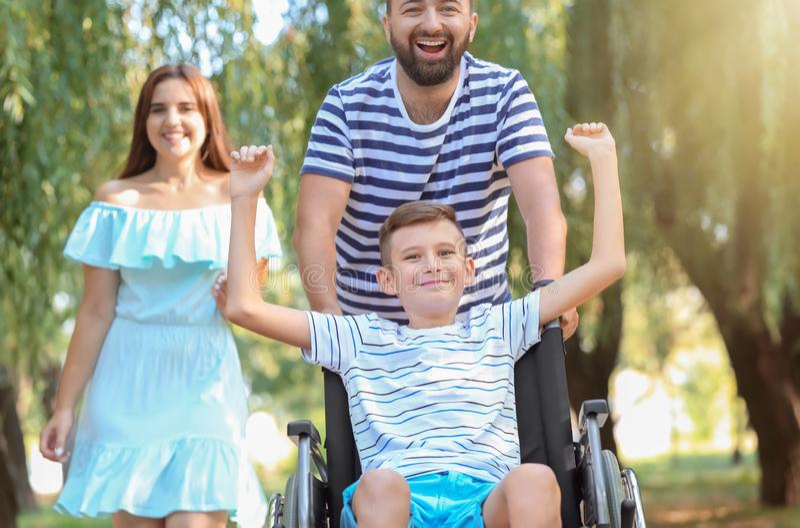 Adolescent dans le fauteuil roulant avec sa famille marchant dehors photo libre de droits