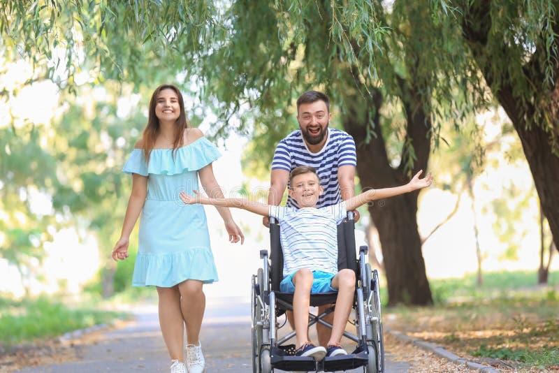 Adolescent dans le fauteuil roulant avec sa famille marchant dehors image libre de droits