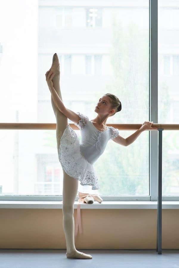 Adolescent de ballerine étirant la jambe au barre de ballet image stock