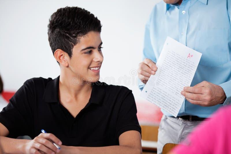 Adolescent de professeur Holding Paper With au bureau image stock