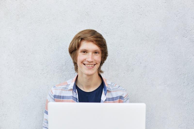 Adolescent de sourire avec l'aspect attrayant se reposant au-dessus du fond blanc utilisant l'ordinateur portable pour les films  photos stock