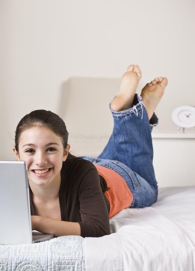 Adolescent de sourire sur l'ordinateur portatif photo stock