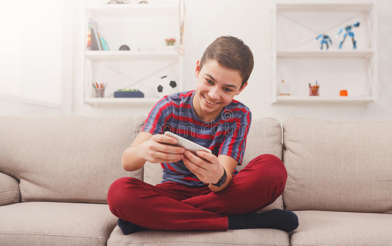 Adolescent enthousiaste jouant le jeu mobile à la maison photographie stock