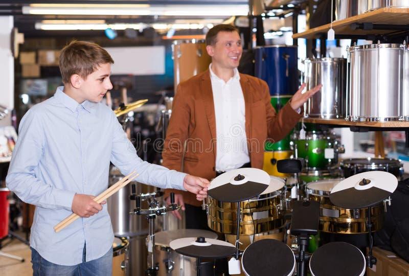 Adolescent et père décidant de l'unité à tambour dans la boutique musicale photos libres de droits