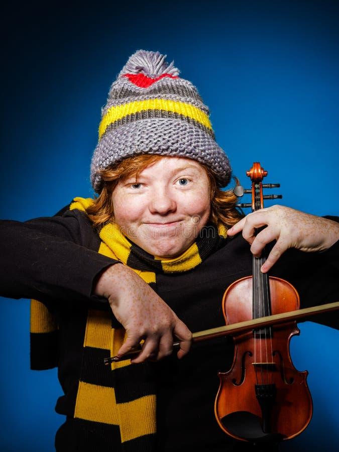 Adolescent expressif roux jouant le violon, concept drôle image stock