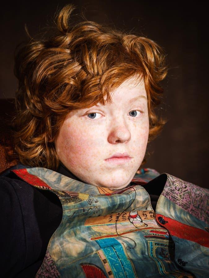 Adolescent expressif roux s'asseyant dans le fauteuil photo stock