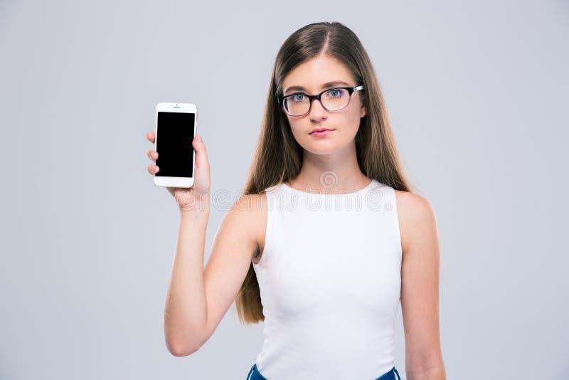 Adolescent féminin en verres montrant l'écran vide i de smartphone images stock