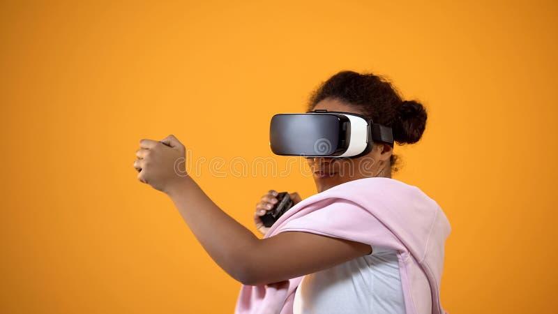 Adolescent féminin enthousiaste dans le casque de vr appréciant le jeu sur Internet, technologie moderne photographie stock