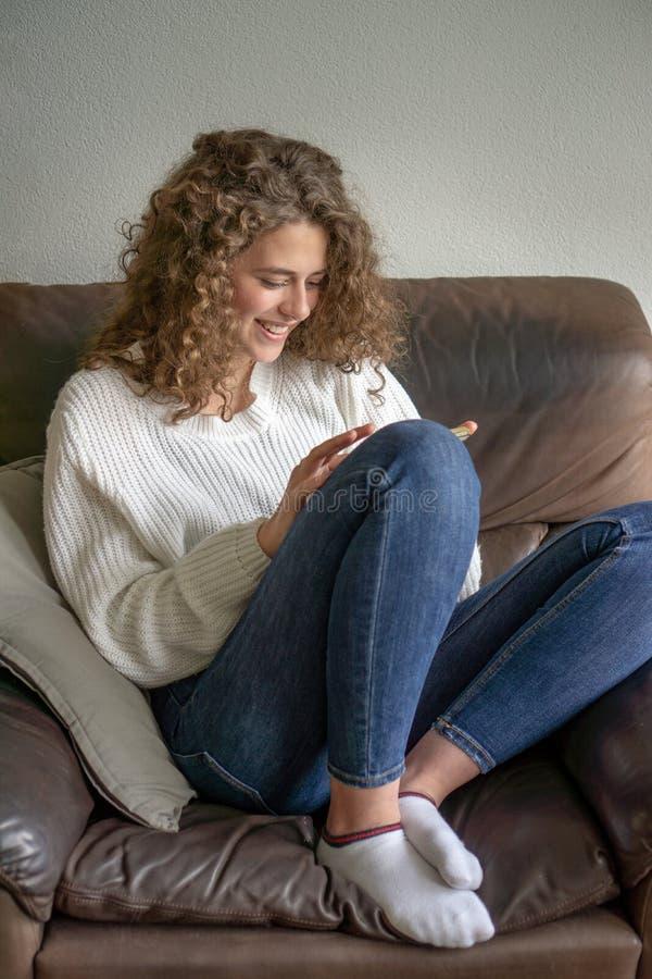 Adolescent féminin s'asseyant dans une chaise étant occupée avec elle téléphone photos stock