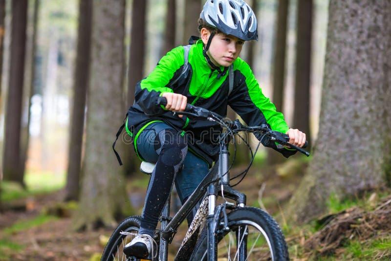 Adolescent faisant du vélo sur des traînées de forêt image libre de droits
