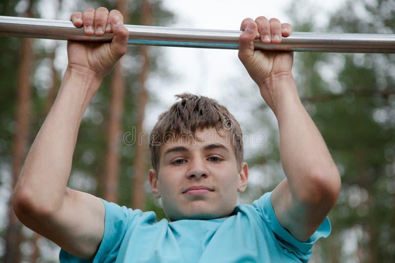 Adolescent faisant l'exercice sur une barre horizontale photographie stock libre de droits