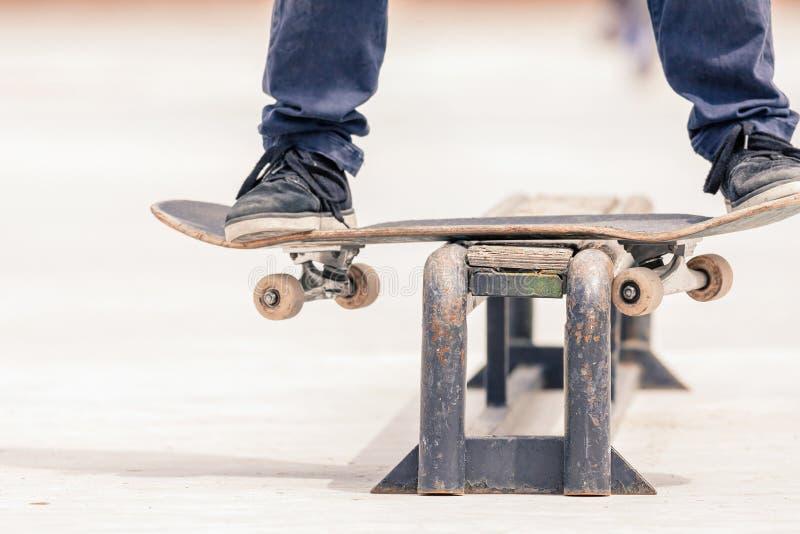 Adolescent faisant un tour par la planche à roulettes sur un rail en parc de patin image stock