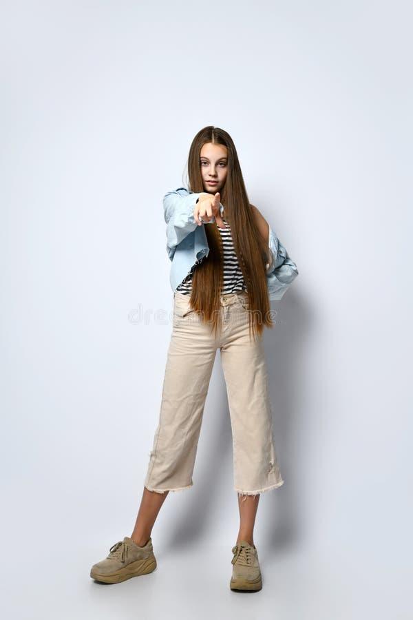 Adolescent in gestript T-shirt, sneakers, denim jack en broek Ze wijst naar jou, en staat geïsoleerd voor wit Volledige lengte stock foto's