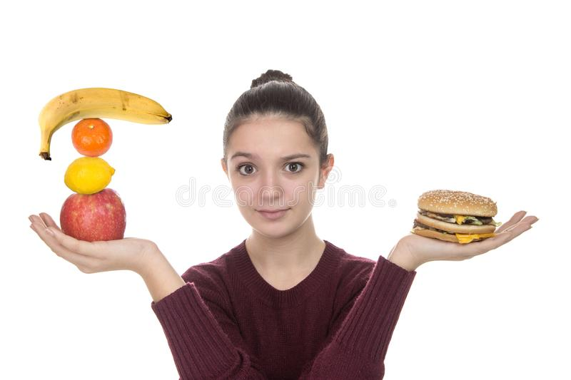 Young girl with fruit and a hamburger royalty free stock photos