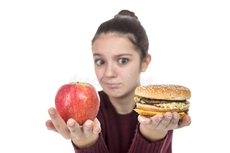 Young Girl with a hamburger and an apple royalty free stock photo