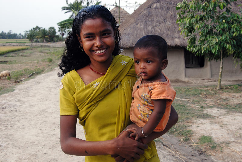 Adolescent Girl in rural India. April 20,2012 Amlamethi,Gosaba,Sundarban,West Bengal,India,Asia-An adolescent girl holding a child at the remote village of India royalty free stock photo