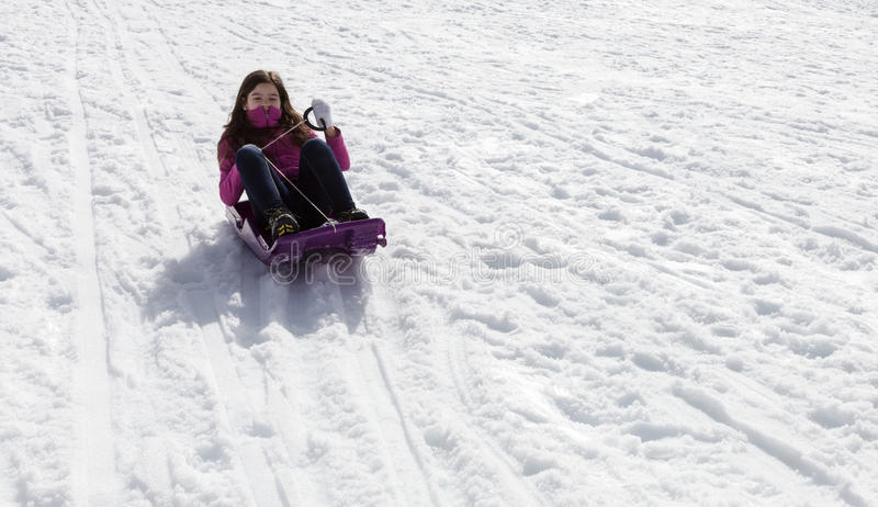 Adolescent girl sledding. Adolescent girl on sled in snow stock photos