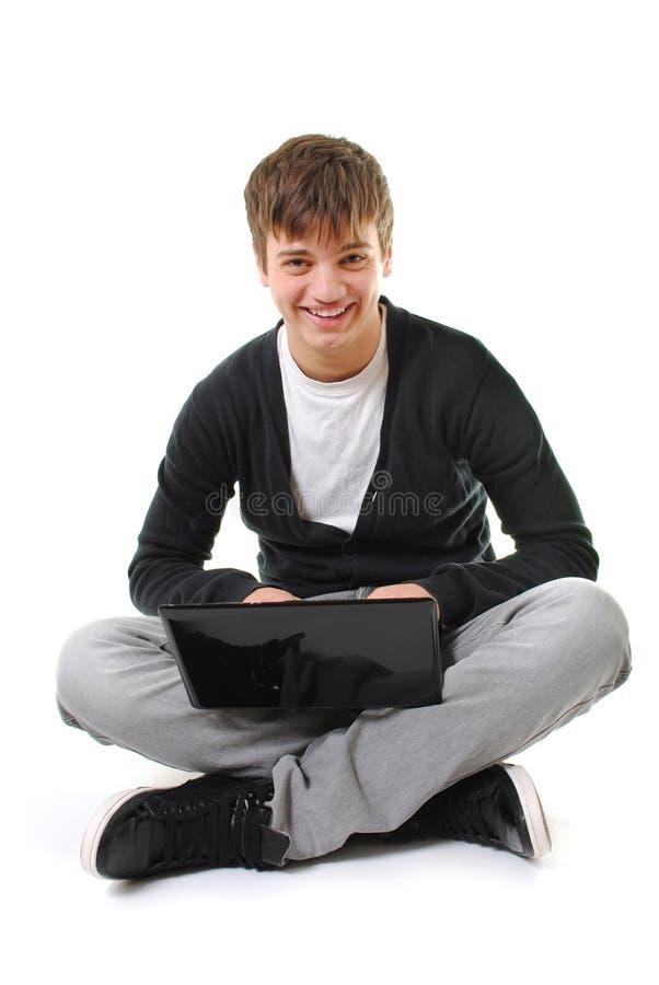 Adolescent heureux avec l'ordinateur portatif d'isolement photo libre de droits