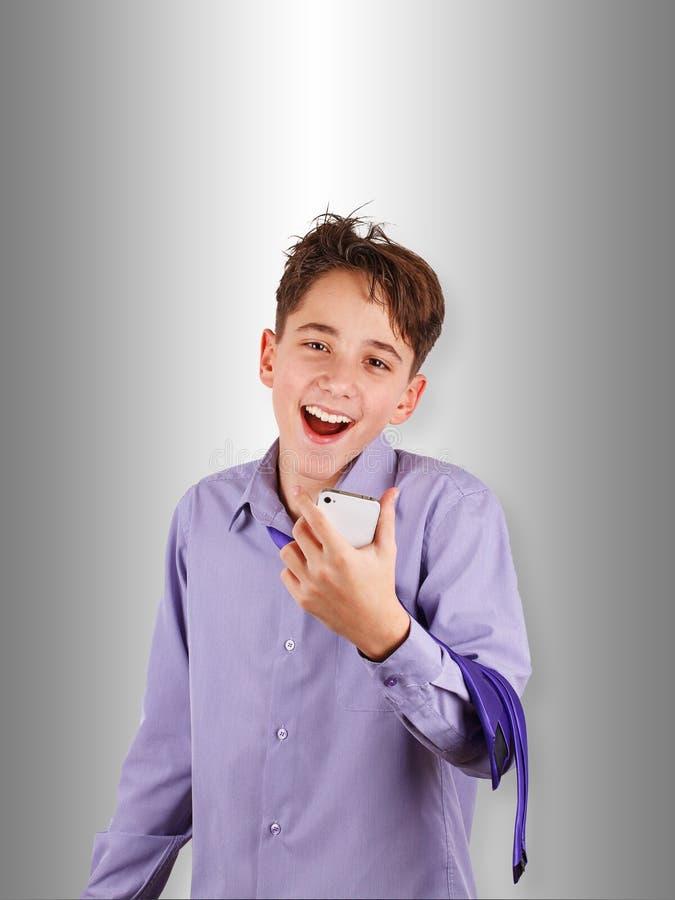 Adolescent heureux dans la chemise et lien écoutant la musique, dactylographiant au téléphone portable ou faisant le selfie photographie stock libre de droits