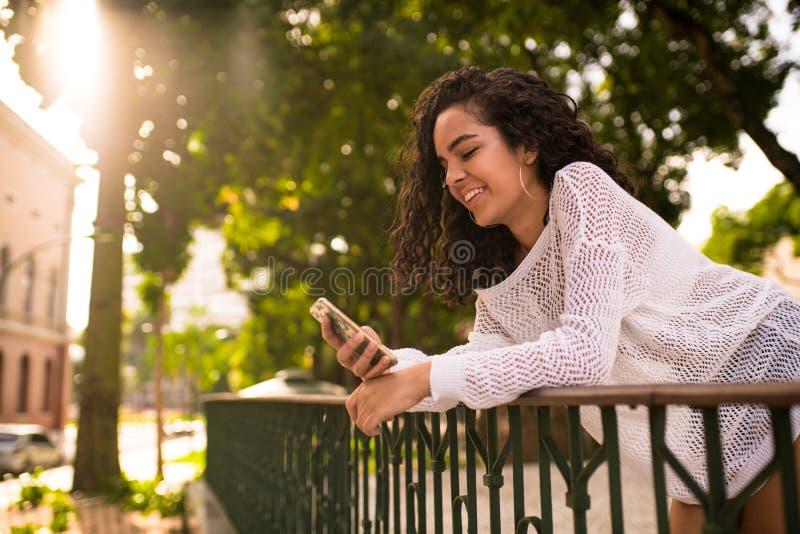 Adolescent heureux regardant le téléphone portable photo stock