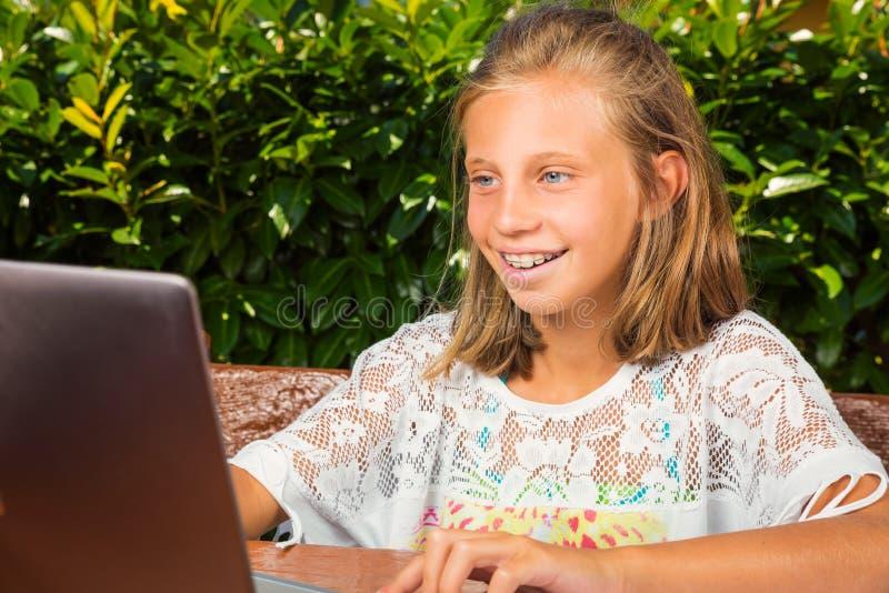Adolescent heureux sur l'ordinateur image stock