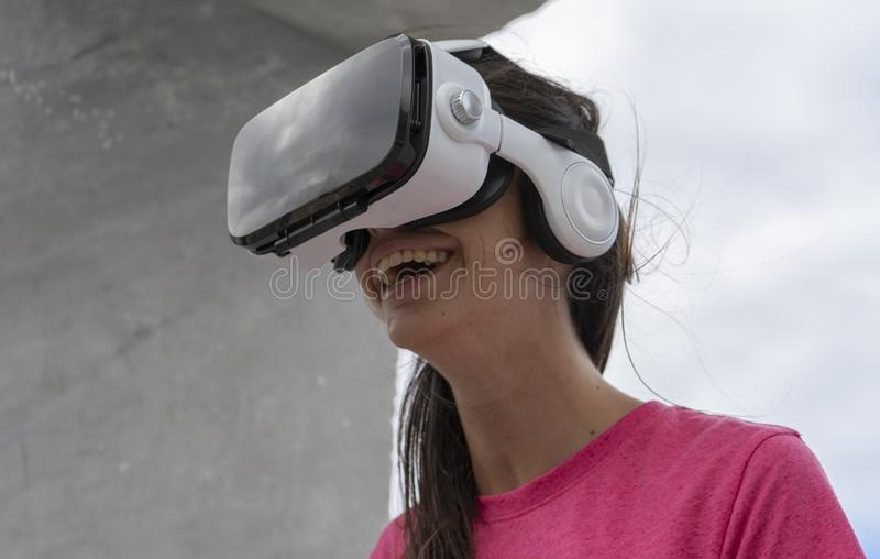 Adolescent interacting with innovative tech virtual reality glasses smiling and playing, touching a dream. Lady reaching visual royalty free stock photos