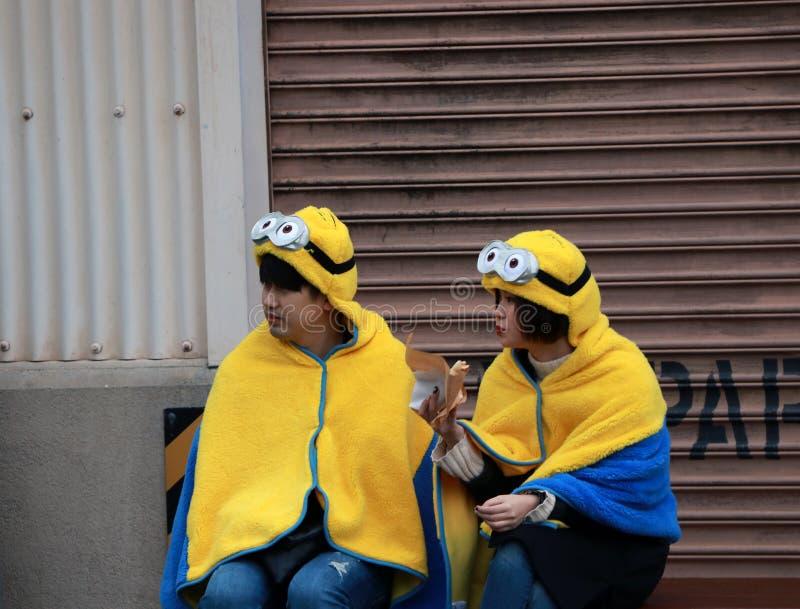 Adolescent japonais de fille et de garçon dans le capot et la couverture du subordonné aux studios universels Japon photo libre de droits