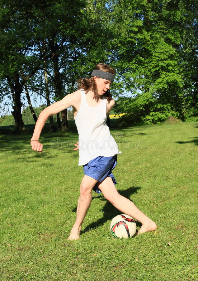 Adolescent jouant le football image stock