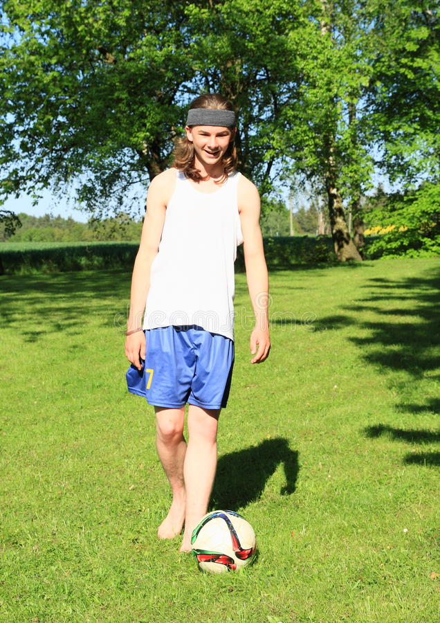 Adolescent jouant le football photos stock