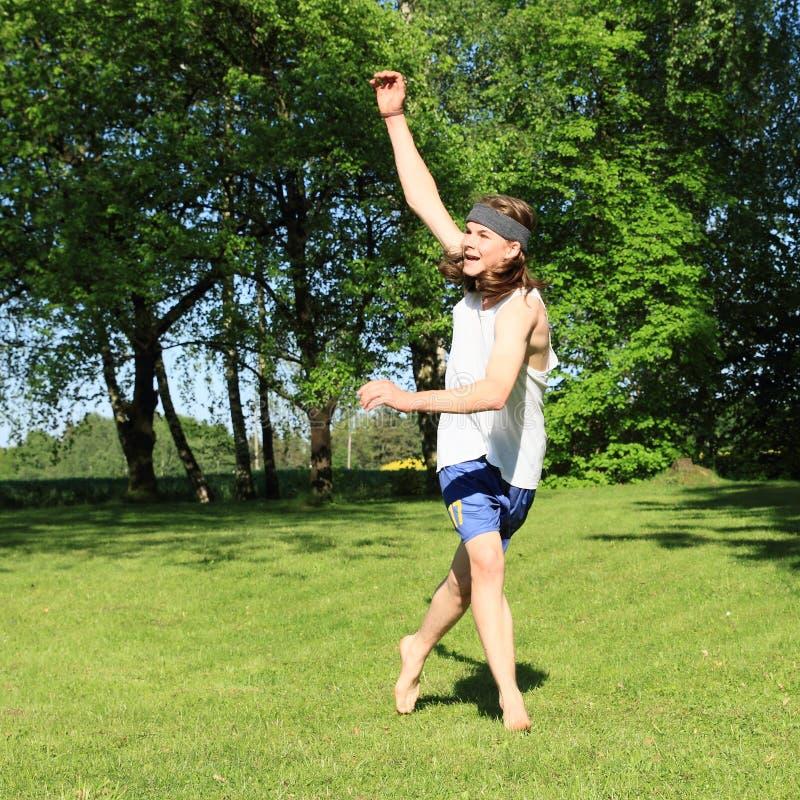 Adolescent jouant sur le pré photographie stock libre de droits