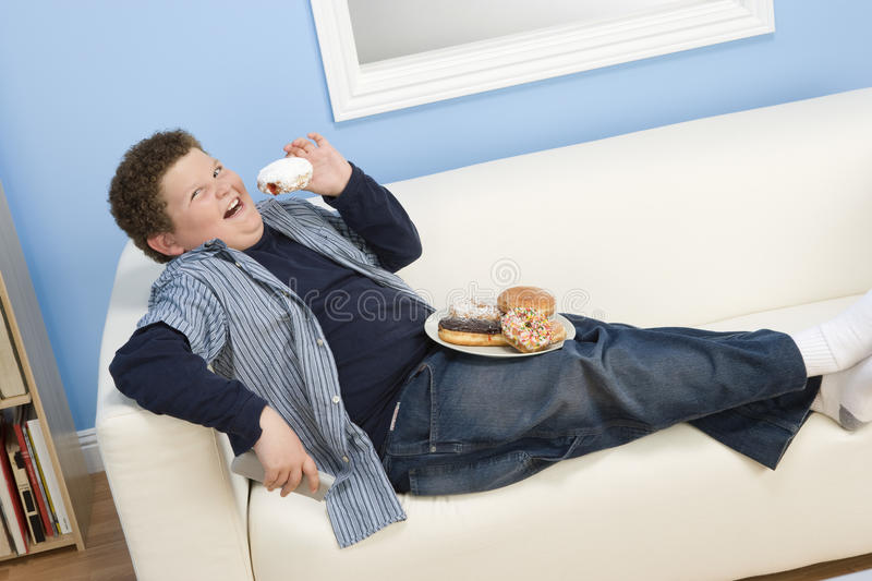 Adolescent mangeant le beignet image stock