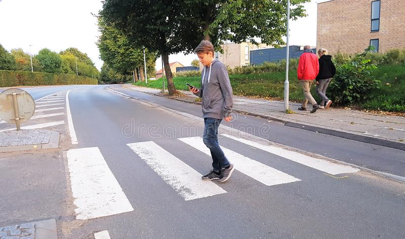 Adolescent marchant à travers la route tout en regardant son smartphone photos libres de droits