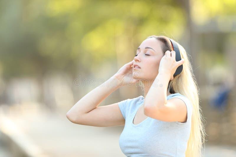 Adolescent mettant des écouteurs dans un parc photo libre de droits