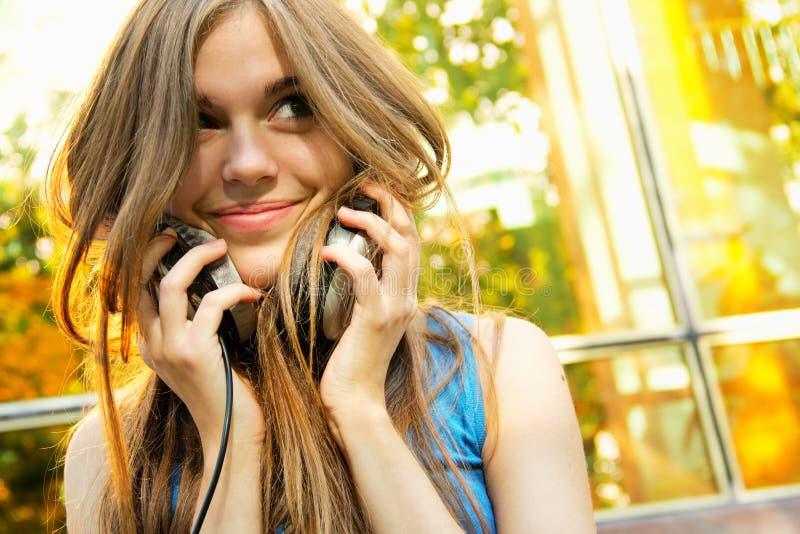 Adolescent mettant sur des écouteurs photos stock