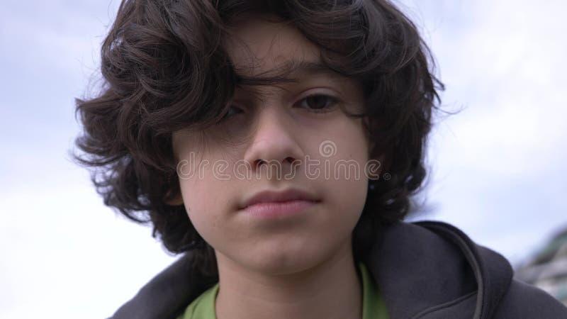 Adolescent mignon avec les cheveux boucl?s contre le ciel bleu 4k, tir au ralenti images stock