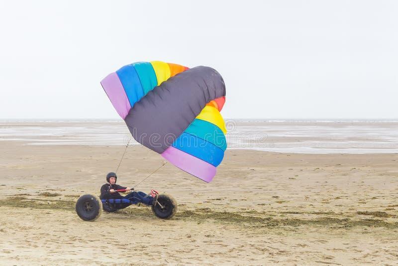 Adolescent néerlandais conduisant le boguet avec le cerf-volant sur la plage image libre de droits