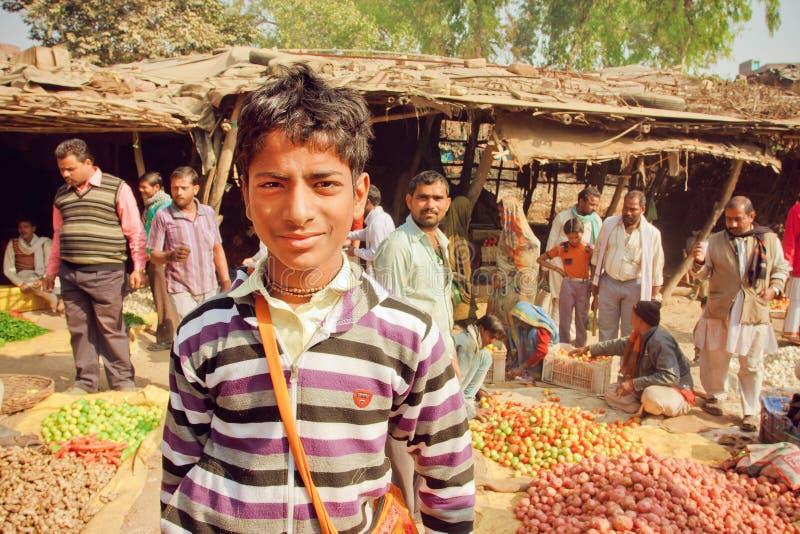 Adolescent non identifié se tenant dans la foule des clients du marché végétal de village dans l'Inde image stock