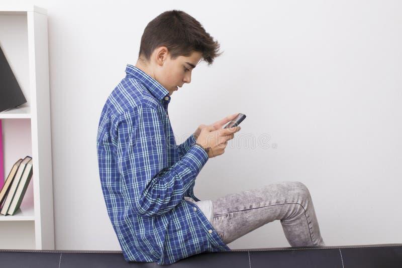 Adolescent ou préadolescent avec le téléphone portable photographie stock