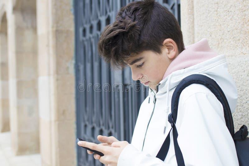 Adolescent ou préadolescent sur la rue avec le téléphone portable images stock
