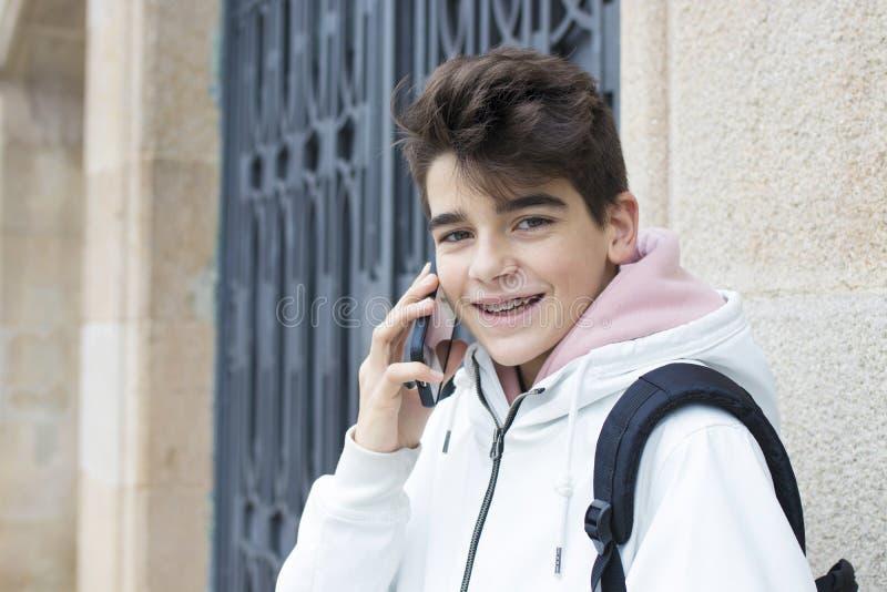 Adolescent ou préadolescent sur la rue avec le téléphone portable photographie stock