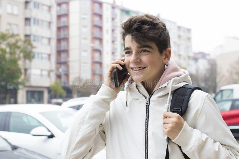 Adolescent ou préadolescent sur la rue avec le téléphone portable photo stock