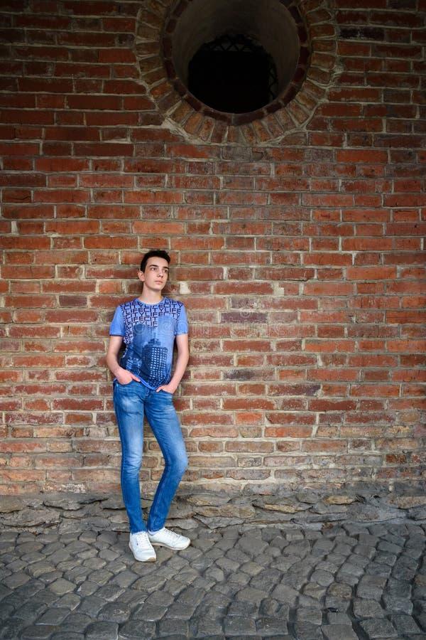 Adolescent près de vieux mur de briques sur la rue photographie stock libre de droits