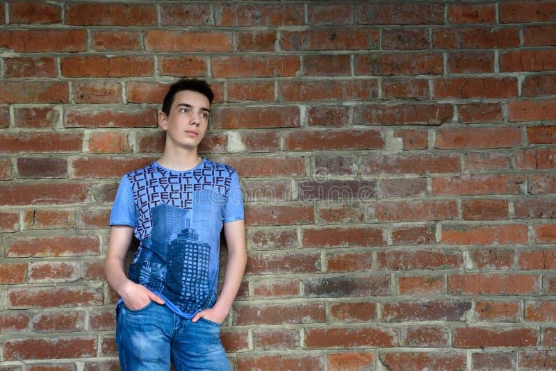 Adolescent près de vieux mur de briques sur la rue photos stock