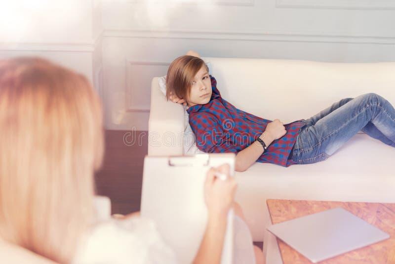 Adolescent préoccupé se trouvant sur le divan pendant la session psychologique photos stock