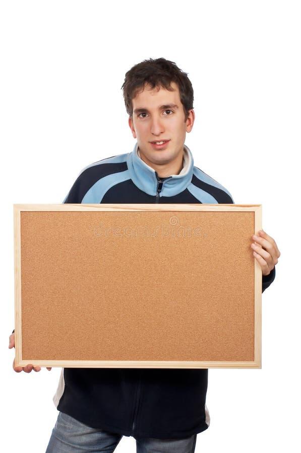 Adolescent retenant le corkboard image stock
