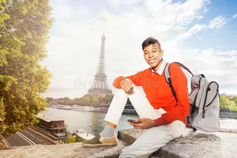 Adolescent s'asseyant contre Tour Eiffel avec le téléphone photo libre de droits