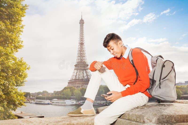 Adolescent s'asseyant contre Tour Eiffel avec le téléphone photo stock